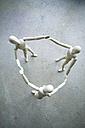 Three wooden manikins holding hands on grey ground - MYF000717