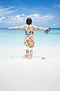 Maledives, Ari Atoll, young woman with outstretched arms standing in water at seafront - FLF000587