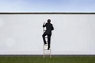 Business man climbing on carrier ladder - RBF002221