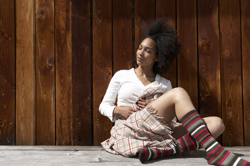 Sunbathing young woman leaning on wooden wall - FSF000403