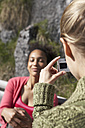 Switzerland, woman taking a photo of her female friend - FSF000362