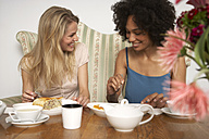 Two female friends eating cake and drinking tea in a cafe - FSF000352