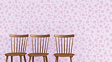 Row of three wooden chairs in front of pink wallpaper with floral design - UWF000267