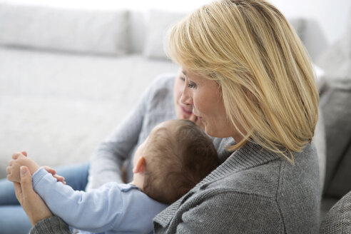 Mother sitting with daughter and baby boy on couch - GDF000590