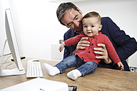 Businessman with baby boy working from home - GDF000613
