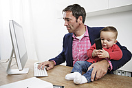 Businessman with baby boy working from home - GDF000616