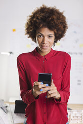 Portrait of young female afro architect with smartphone at her office - EBSF000364