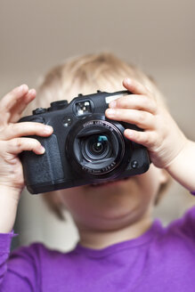 Little girl's face behind digital camera - JFEF000535