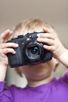 Little girl's face behind digital camera - JFEF000535