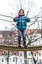 Little girl standing on playground equipment - JFEF000536