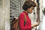 Young woman with bck pack hearing music with earphones - EBSF000366