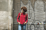 Smiling young woman standing in front of roller shutter with graffiti - EBSF000370