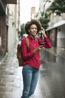 Portrait of smiling young woman hearing music with earphones - EBSF000375