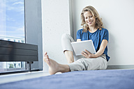 Portrait of smiling mature woman sitting with digital tablet on the floor in her apartment - RBF002037