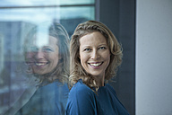 Portrait of smiling mature woman leaning at window in her apartment - RBF002040