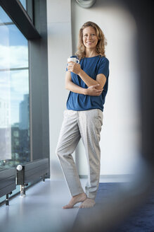 Smiling mature woman with mug standing  at her apartment - RBF002043
