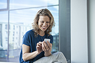 Smiling mature woman using her smartphone at home - RBF002046