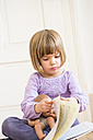 Portrait of little girl turning pages of a songbook - LVF002304