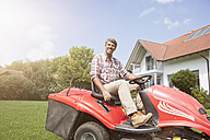 Man on riding lawn mower in garden - RBF001902