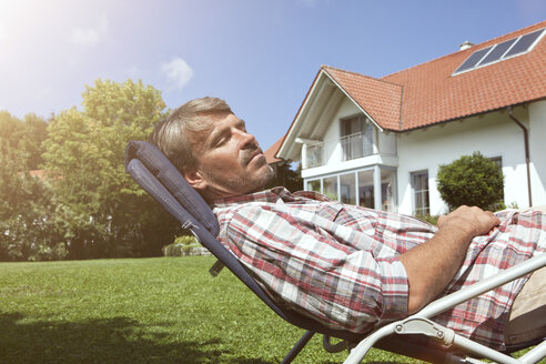 Relaxed man in deck chair in garden - RBF001905