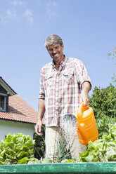Man watering plants in garden - RBF001923