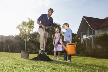 Father and children planting tree in garden - RBF002018
