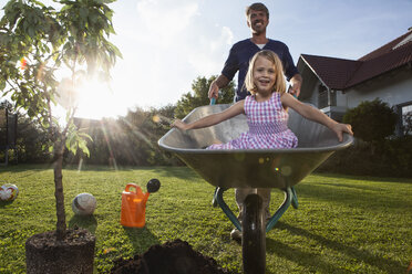 Father with daughter in wheelbarrow planting tree in garden - RBF002021