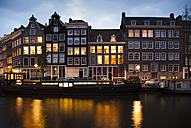 Netherlands, Amsterdam, view to row of lighted old residential houses at town canal by evening twilight - FCF000475