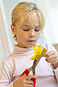 Little girl tinkering with scissors and paper - JFEF000554