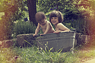 Baby and girl in tub in garden - LVF002322