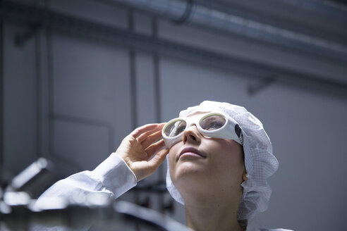 Young female technician with protective cap and safety glasses looking up in a labroratory - SGF001167