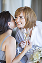 Bride and bridesmaid drinking champagne glasses while getting ready for wedding - ZEF002521