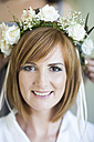 Portrait of smiling young woman wearing floral hair wreath - ZEF002524