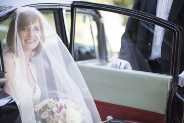 Smiling bride getting out of car before her wedding - ZEF002564