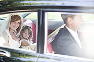 Bride sitting in car with little bridesmaid and driver before wedding - ZEF002571
