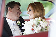 Happy bride and groom in car - ZEF002576