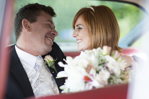 Happy bride and groom in car - ZEF002576