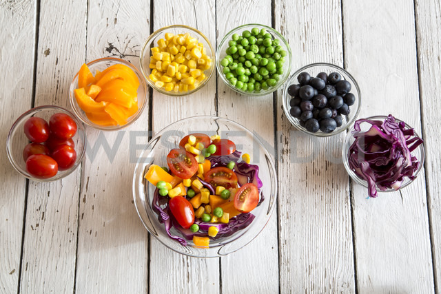 Mixed salad and glass bowls with different raw vegetables  rainbow-coloured arranged on white wood - SARF001055