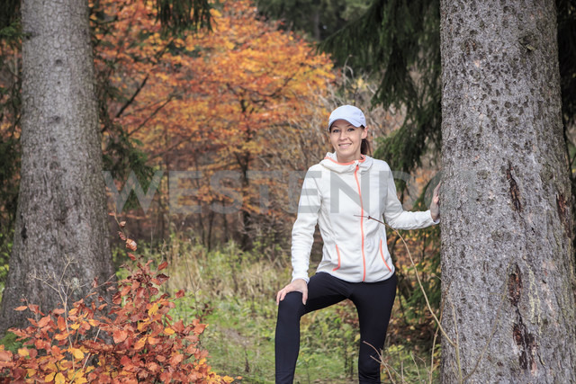 Portrait of female jogger leaning on tree trunk in the wood - VTF000351 - Val Thoermer/Westend61