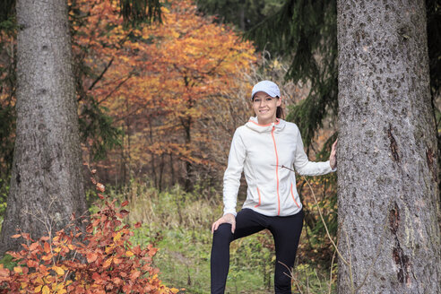 Portrait of female jogger leaning on tree trunk in the wood - VTF000351