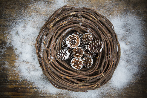 Wreath, fir cones and artificial snow on dark wood - LVF002330