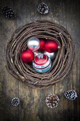 Wreath, Christmas baubles and fir cones on dark wood - LVF002332