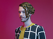 Portrait of fashionable dressed young man with curly hair in front of red background - RH000446
