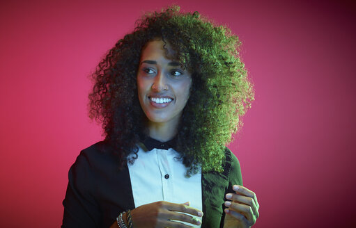 Portrait of smiling young woman with Afro in front of red background watching something - RHF000434