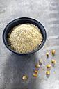 Bowl of cornmeal and maize grains on metal - EVGF001015