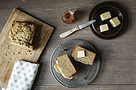 Slices of home-baked glutenfree buckwheat bread, pieces of butter and glass can with honey on wood - EVGF001019