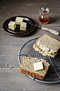 Slices of home-baked glutenfree buckwheat bread and piece of butter on cooling grid - EVGF001021