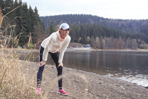 Female jogger having a rest at lakeshore - VTF000356