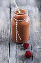 Glass of raspberry smoothie on grey wood - ODF000884