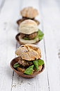 Three garnished bread rolls with patty and lamb's lettuce on wood - ODF000886
